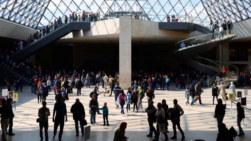 Des touristes sous la pyramide du Louvre - Paris (France)