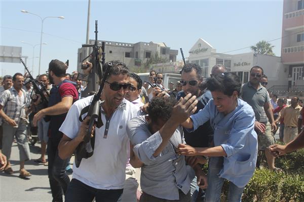 Un homme, suspecté d'avoir pris part à l'attaque, est escorté par la police tunisienne alors qu'une femme tente de le frapper (Reuters).